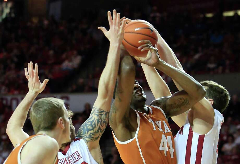 Oklahoma forward Tyler Neal, right, and forward Ryan Spangler defend as Texas center Prince Ibeh (44) goes to the basket during the second half of an NCAA college basketball game in Norman, Okla., Saturday, March 1, 2014. Oklahoma won 77-65. (AP Photo/Alonzo Adams) Photo: Alonzo Adams, Associated Press / FR159426 AP