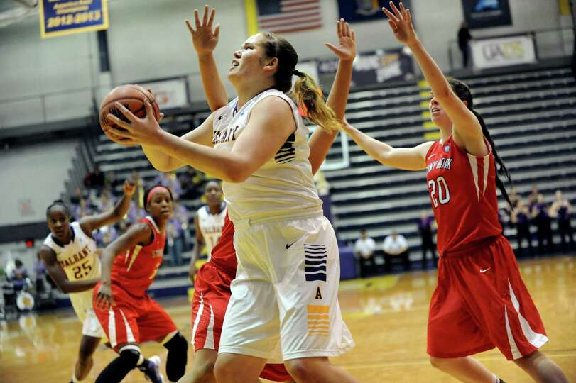 UAlbany's Megan Craig, center, looks to the hoop during their basketball game against Stony Brook on