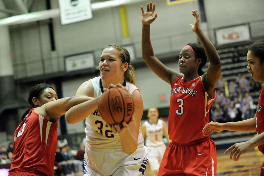 UAlbany's Megan Craig, center, hangs onto a rebound as Stony Brook's Sabre Proctor, left, and Jessica Ogunnorin defend during their basketball game on Saturday, March 1, 2014, at UAlbany in Albany, N.Y. (Cindy Schultz / Times Union) Photo: Cindy Schultz / 00025922A