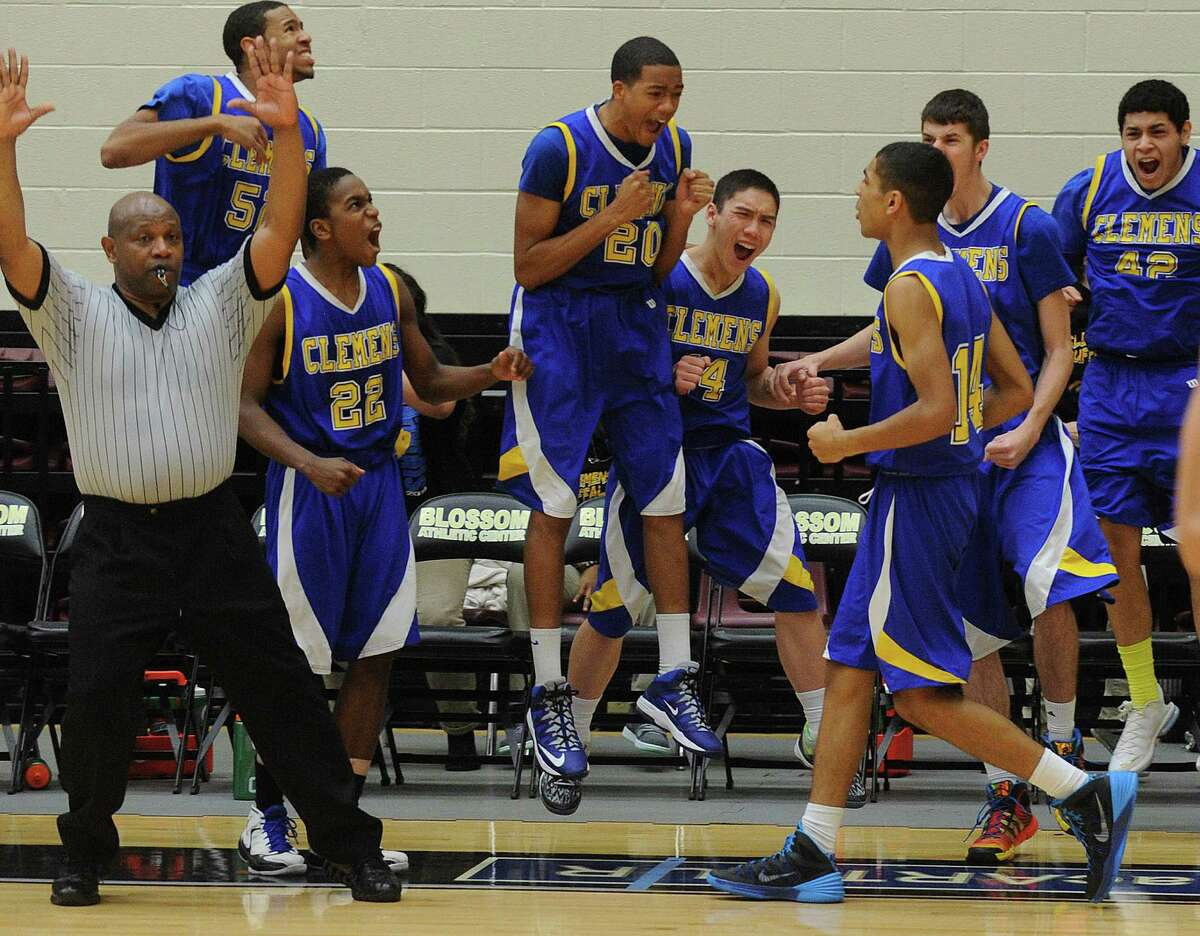 Clemens basketball players celebrate after teammate Devin Kearns (14) hit a game-winning three-point shot at the end of overtime to defeat Hays, 69-66, in the boys Region IV-4A final at Littleton Gym on Saturday, March 1, 2014.