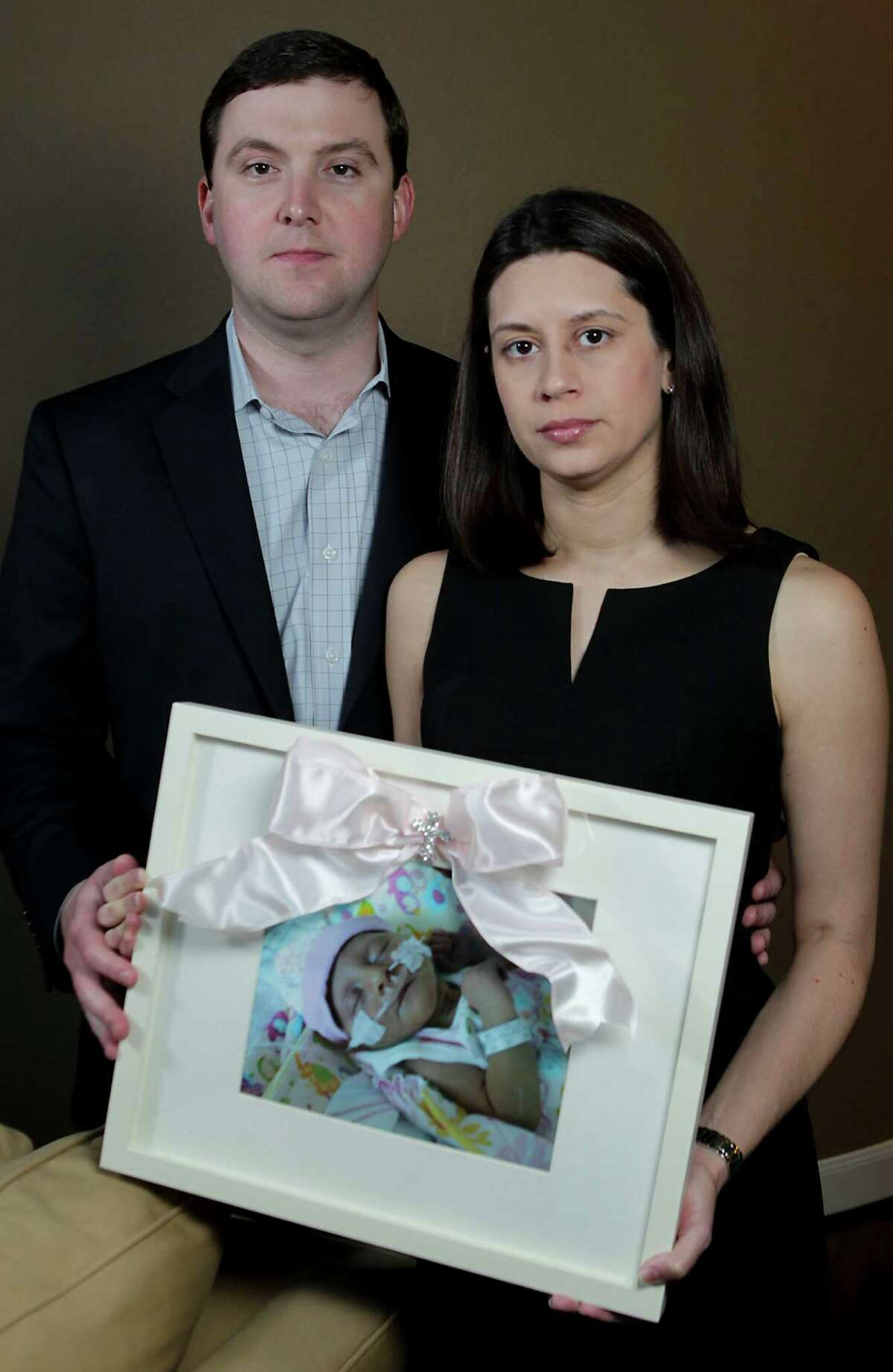 Farah and Patrick Armstrong of Katy hold a picure of their daughter Madeline Leigh Armstrong, who died of CMV, a rare viral infection.