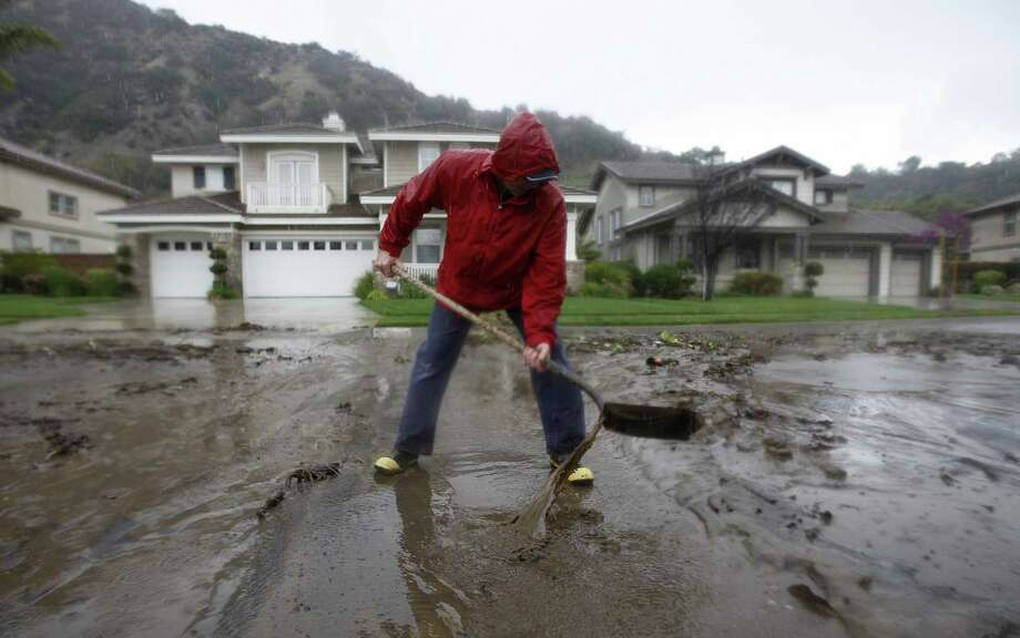 Bob Lavezzari clears mud from his street in an Azusa, Calif., neighborhood threatened with a possible major mudslide below a burned hillside as a major storm brings rain amid a drought. Photo: David McNew / Getty Images / 2014 Getty Images