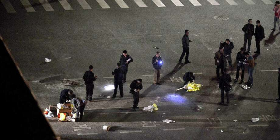 Police investigate the crime scene outside a railway station after an attack by knife-wielding men left dozens dead in Yunnan province in southwest China. Photo: Associated Press / CHINATOPIX