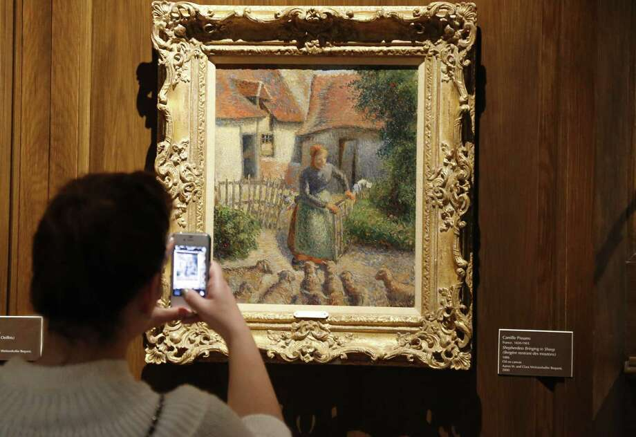 """A visitor to the art museum at the University of Oklahoma photographs """"Shepherdess Bringing in Sheep"""" by French impressionist artist Camille Pissarro. Photo: Sue Ogrocki / Associated Press / AP"""