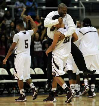 Beaumont Central assistant coach Joseph Fontenaux, Jr. is carried off the court in celebration by Nijal Pearson following the Jaguars' 67-57 victory over Marshall in the Class 4A Region 3 Final high school basketball playoff game, Saturday, March 1, 2014, at Merrill Center in Katy, TX. Photo: Eric Christian Smith, For The Chronicle