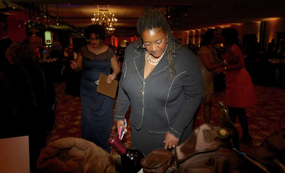 Elicia Spearman, of Cheshire, looks over the items up for silent auction during the Hord Foundation 20th Anniversary Gala at the Amber Room Colonnade, Danbury, Conn, on Saturday night, March 1, 2014. Photo: H John Voorhees III / The News-Times Freelance
