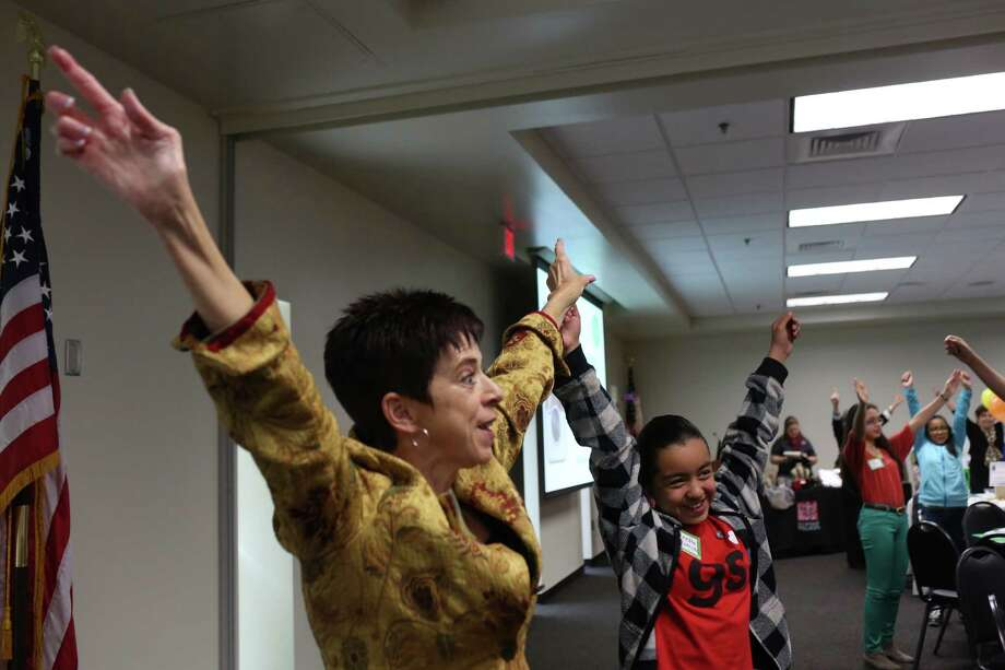 """Tracy Tylman teaches """"power posing"""" with the help of participant Jeanette Ramirez, 12, during the Women's Global Connection Girls' Global Summit at the University of the Incarnate Word Rosenberg School of Optometry. Photo: Lisa Krantz / San Antonio Express-News / SAN ANTONIO EXPRESS-NEWS"""