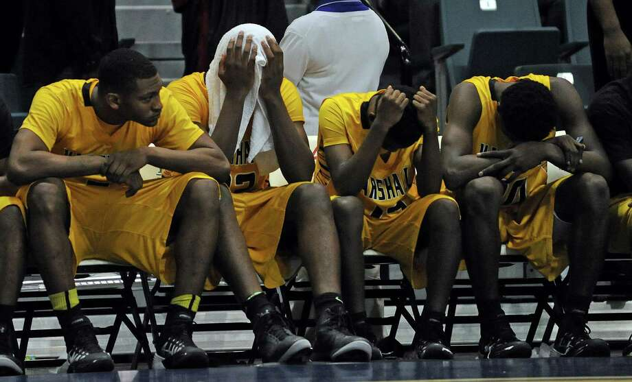 Marshall's Elliot Taylor, second from left, and teammates sit dejectedly on the bench in the waning moments of their 67-57 loss to Beaumont Central during the second half of the Class 4A Region 3 Final high school basketball playoff game, Saturday, March 1, 2014, at Merrill Center in Katy, TX. Photo: Eric Christian Smith, For The Chronicle