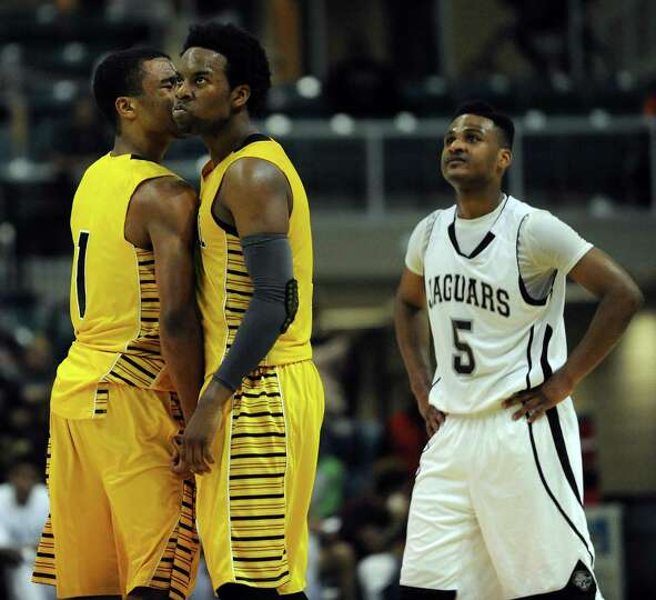 Marshall's D.J. Day, center, reacts after being fouled as teammate Oscar Wilhite, left, celebrates a