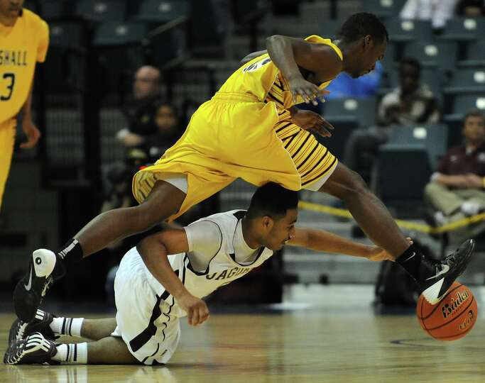 Beaumont Central's Jacory Guillory, bottom, and Marshall's Shanr Rogers chase after a loose ball dur