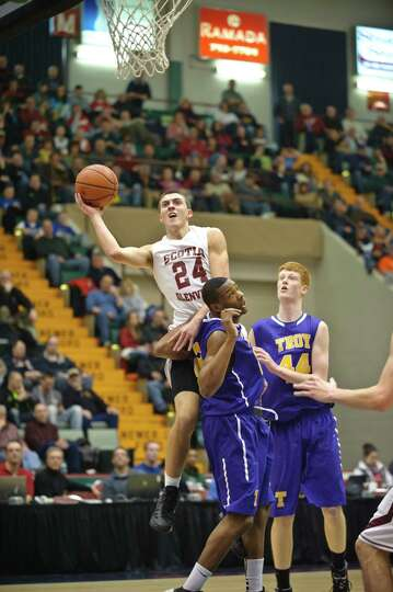 Scotia Glenville's Joe Cremo goes up for a basket against Troy's Maurice Watson and Jack McLaren dur