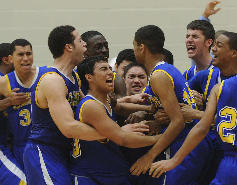 Clemens players mob Devin Kearns (front right) after his 3-pointer at the overtime buzzer lifted the Buffaloes to a 69-66 Region IV-4A final victory over Hays on Saturday at Littleton Gym. Photo: Billy Calzada / San Antonio Express-News / San Antonio Express-News
