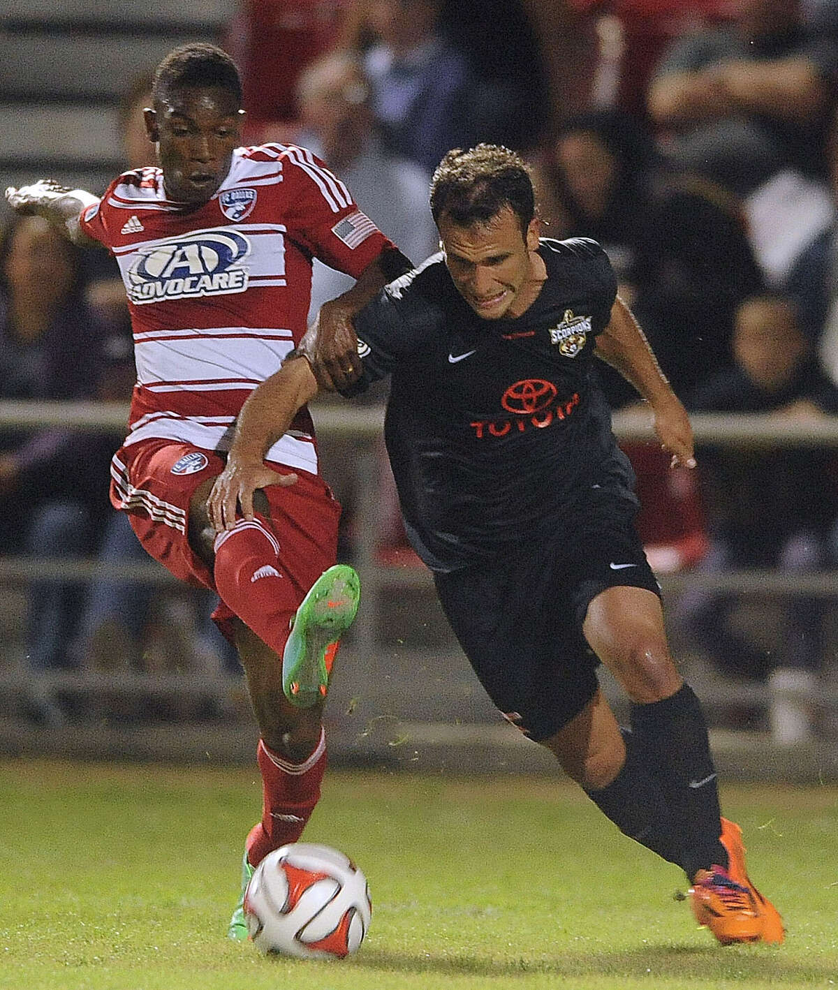 Fabian Castillo of FC Dallas, left, attempts to kick the ball as Julio Garcia of the San Antonio Scorpions gives chase during a soccer friendly at Toyota Field Saturday, March 1, 2014.