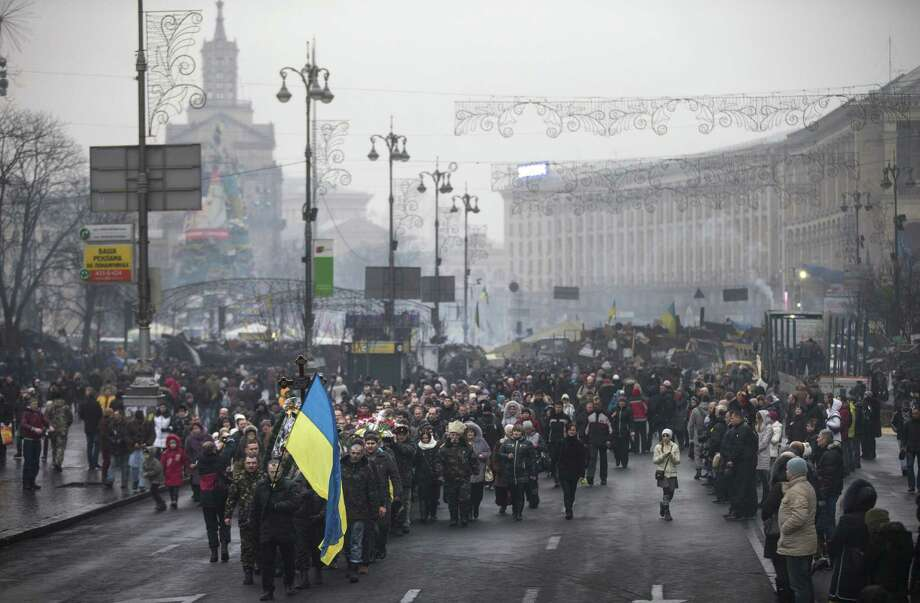 People march carrying Ukrainian flags during a funeral for a protester who was killed in clashes with police in Kiev, where fears are growing that separatist upheaval will fracture the country. Photo: Uriel Sinai / New York Times / NYTNS