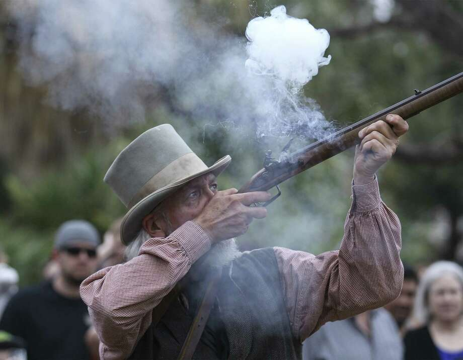 Living history volunteer Jerry McMann fires his period rifle during a re-enactment and demonstration show at the monthly First Saturday at the Alamo. Photo: Photos By Kin Man Hui / San Antonio Express-News / ©2013 San Antonio Express-News