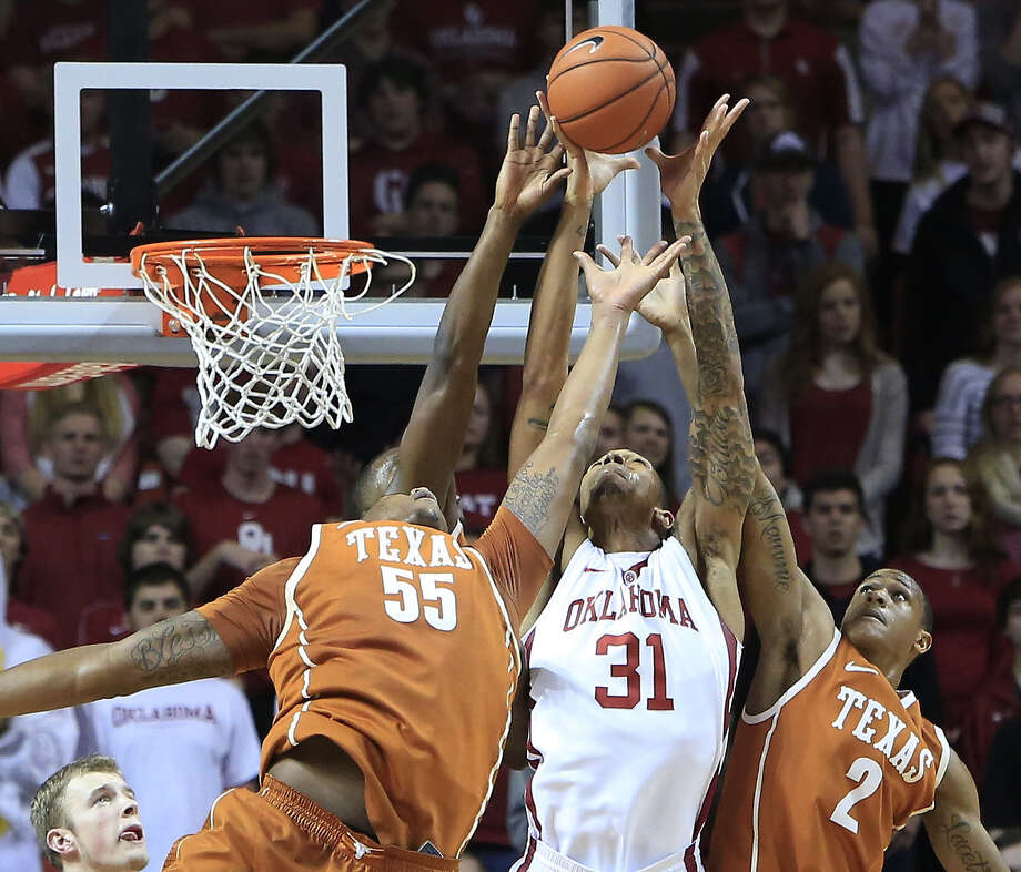 Oklahoma forward D.J. Bennett (center), Texas center Cameron Ridley (left) and Texas guard Demarcus Holland battle for a rebound in the first half. Photo: Alonzo Adams / Associated Press / FR159426 AP
