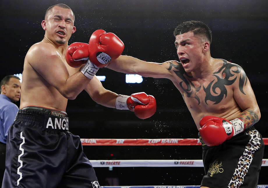 Ivan Najera (right) catches Angel Hernandez with a right hand during their lightweight bout Saturday at the Alamodome. Najera, out of TNT Boxing Club, won by unanimous decision. Photo: Edward A. Ornelas / San Antonio Express-News / © 2014 San Antonio Express-News