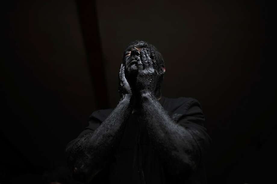 A man covers his face in oil and soot as he gets ready to start a carnival festival in the small village of Luzon, Spain, Saturday, March 1, 2014. Preserved records from the 14th century document Luzon's carnival, but the real origin of the tradition could be much older. Carnival festivals are celebrated in their own way around hundreds of villages in Spain. (AP Photo/Andres Kudacki) Photo: Andres Kudacki, Associated Press