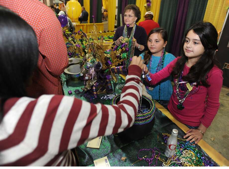 Alisha Jones, right, and Julie James hand Tearria Williams Mardi Gras beads at the Taste of the Triangle event at Ford Park on Tuesday. Photo taken Tuesday, February 12, 2013  Guiseppe Barranco/The Enterprise Photo: Guiseppe Barranco/The Enterprise
