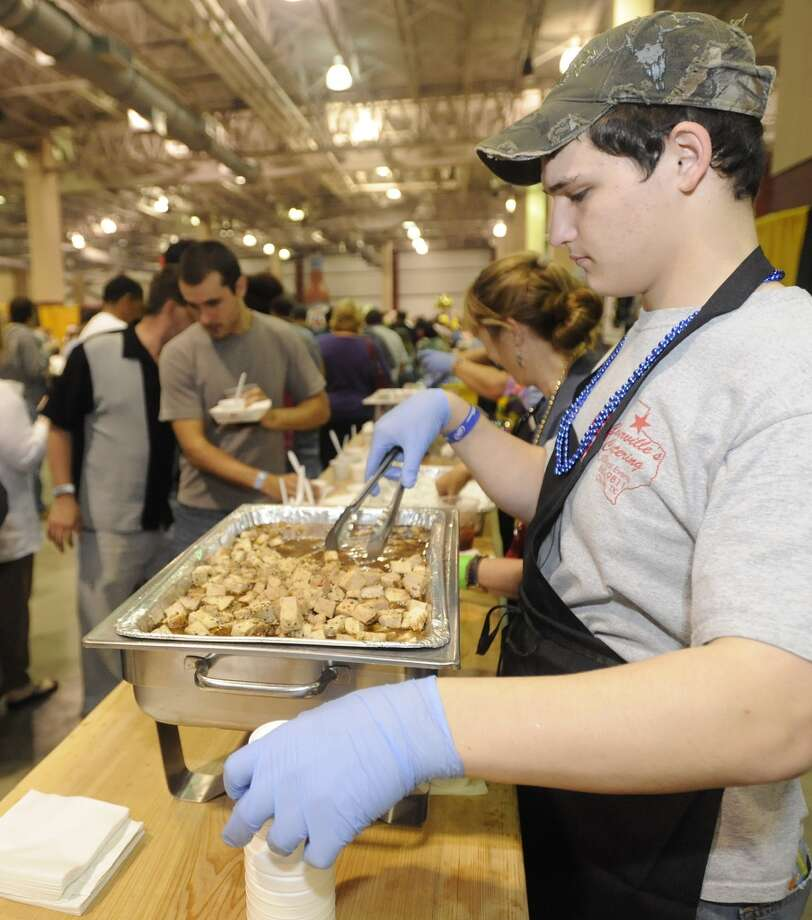 Jacob Muirhead of Courville's Catering, readies more Smoked Pork Loin that is covered in a beer and honey glaze sauce  The annual Taste of the Triangle was held at the Ford Exhibit Hall at Ford Park.  It  featured food booths from all over the area, from country and soul foods, to Tai, Italian, Cajun and Creole foods. This was the 29th annual event put on by the Sabine Area Restaurant Association.    Dave Ryan/The Enterprise Photo: Dave Ryan/The Enterprise
