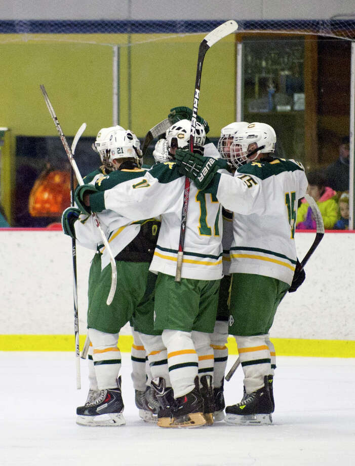 Trinity Catholic players celebrate a goal during Saturday's FCIAC quarterfinal at Terry Conners Rink in Stamford, Conn., on March 1, 2014. Photo: Lindsay Perry / Stamford Advocate