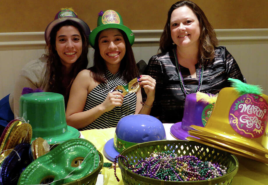 Assumption School coordinators of a Mardi Gras fundraiser Lily Lopez, Michelle Lopez and Cassie Furtek with masks, beads and hats to set the theme for the Saturday event. Photo: Mike Lauterborn / Fairfield Citizen contributed