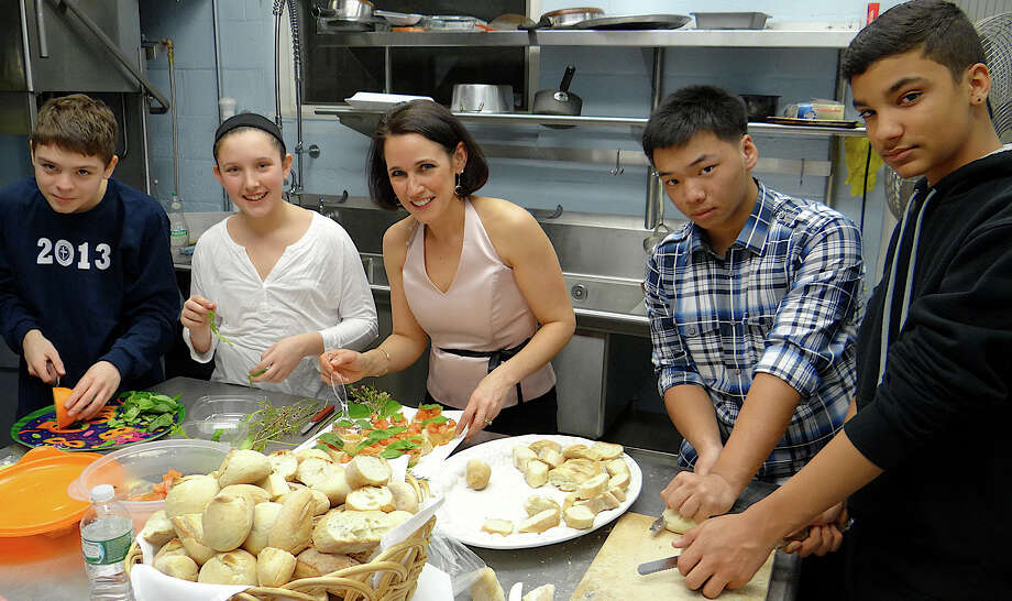 Melinda Gremse, center, prepares food for the Assumption School Mardi Gras fundraiser with students Fred Bennett, Caroline Gremse, Vincent Nguyen and Matthew Boykin. Photo: Mike Lauterborn / Fairfield Citizen contributed