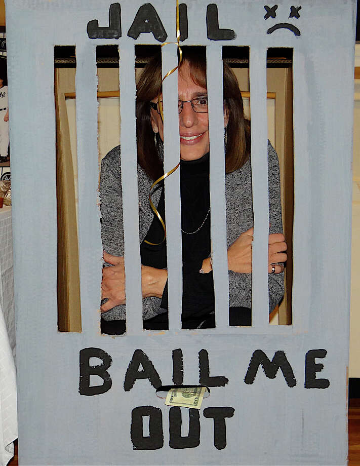 "Assumption Principal Gerrie Desio is ""imprisoned"" in a mock jail waiting to be bailed out through donations at Saturday's Mardi Gras fundraiser for the school. Photo: Mike Lauterborn / Fairfield Citizen contributed"