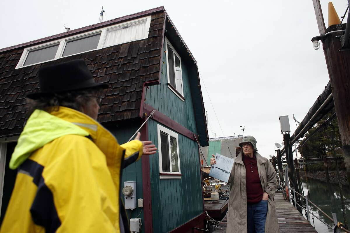 Philip De Andrade, left welcomes neighbor Corinne Woods along the houseboat docks along Mission Creek, Wednesday February 26, 2014, in San Francisco, Calif. Both of them have living among the houseboat community for decades.