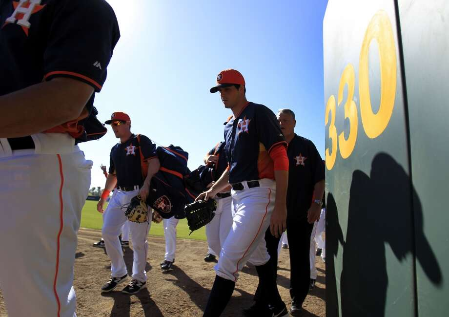 Astros players walk out of the wagon gate in the outfield to stretch at the Osceola County Stadium before the game. Photo: Karen Warren, Houston Chronicle
