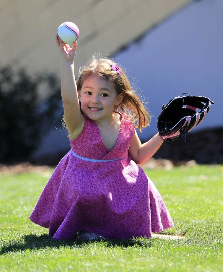 Zeline Borin, 3 1/2, of Atlanta, plays catch with her dad, Tony, during a spring training game Photo: Karen Warren, Houston Chronicle