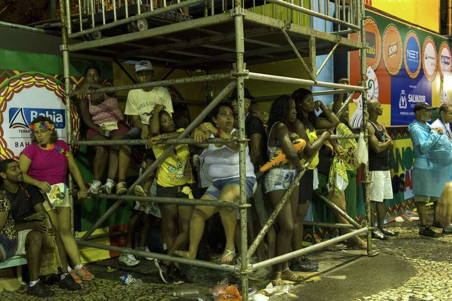 People take a shelter from rain during the carnival on a street in Salvador, northeast of Brazil, on March 2, 2014.  Photo: AFP, Getty Images / 2014 AFP