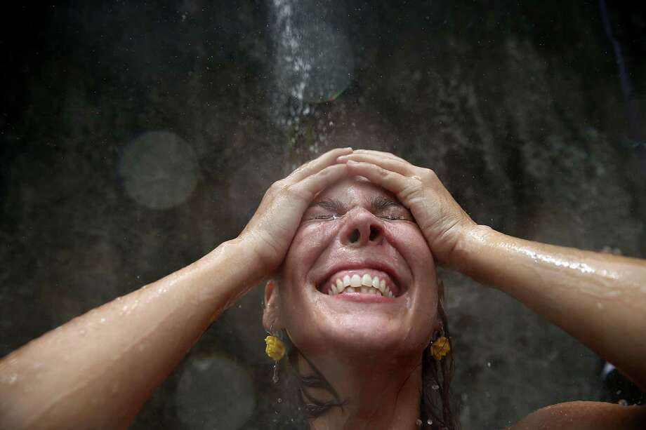 A reveler exalts while being sprayed by water from a resident during the 'Ceu na Terra' street carnival bloco on March 1, 2014 in Rio de Janeiro, Brazil. Carnival is the grandest holiday in Brazil, annually drawing millions in raucous celebrations. Photo: Mario Tama, Getty Images / 2014 Getty Images