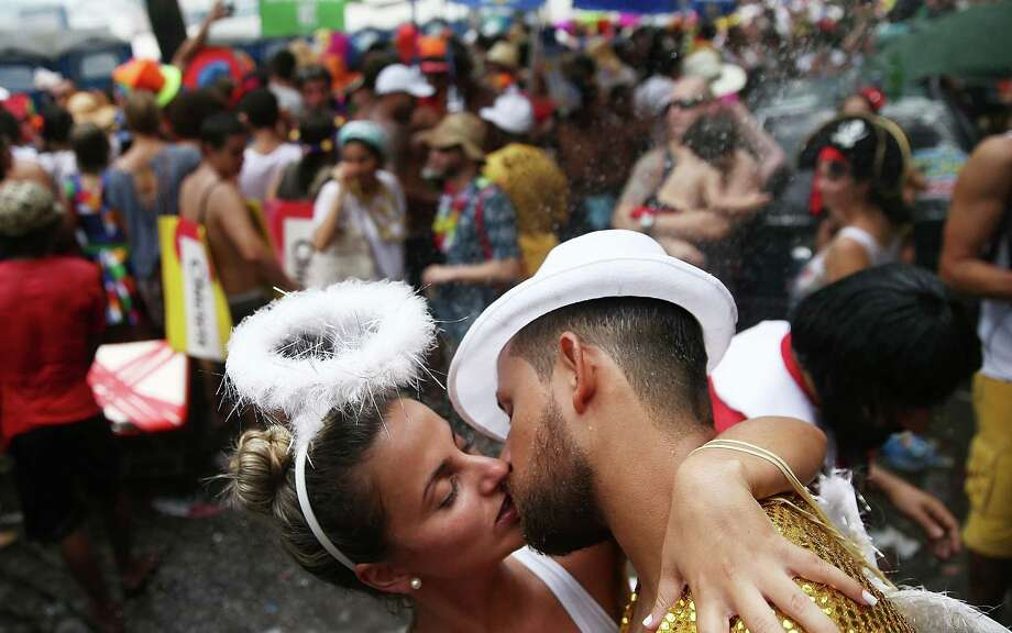 Revelers kiss during the 'Ceu na Terra' street carnival bloco on March 1, 2014 in Rio de Janeiro, Brazil. Carnival is the grandest holiday in Brazil, annually drawing millions in raucous celebrations. Photo: Mario Tama, Getty Images / 2014 Getty Images