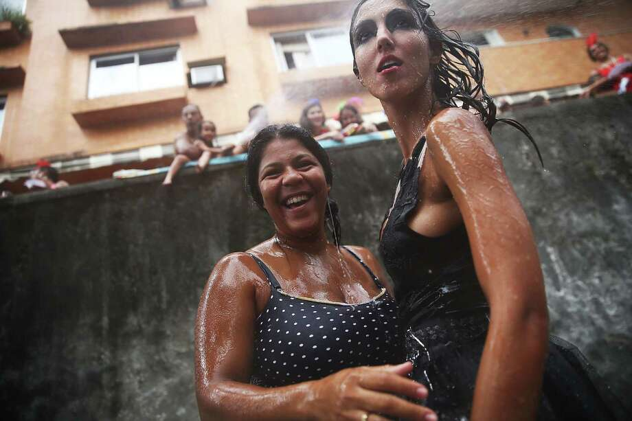 Revelers are sprayed with water during the 'Ceu na Terra' street carnival bloco on March 1, 2014 in Rio de Janeiro, Brazil. Carnival is the grandest holiday in Brazil, annually drawing millions in raucous celebrations. Photo: Mario Tama, Getty Images / 2014 Getty Images