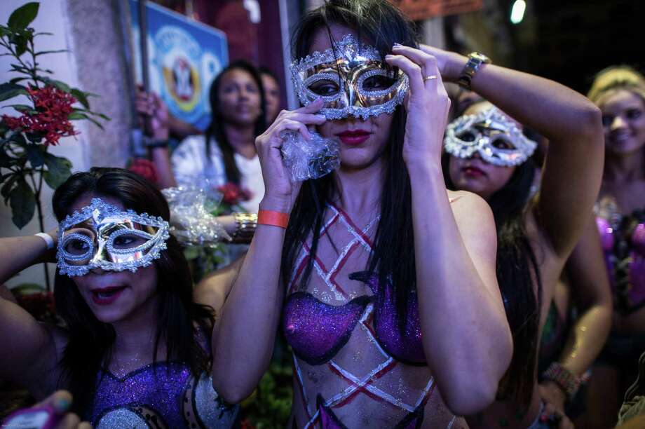 Topless dancers put masks during a street parade of Banda da Rua do Mercado in Rio de Janeiro, Brazil, on Februrary 27, 2014. Rio's carnival will start officially from tomorrow for 5 days and have around 470 groups on streets. Samba school parades will have a peak at Sambodromo on March 2 and 3, 2014. Photo: YASUYOSHI CHIBA, Getty Images / 2014 AFP