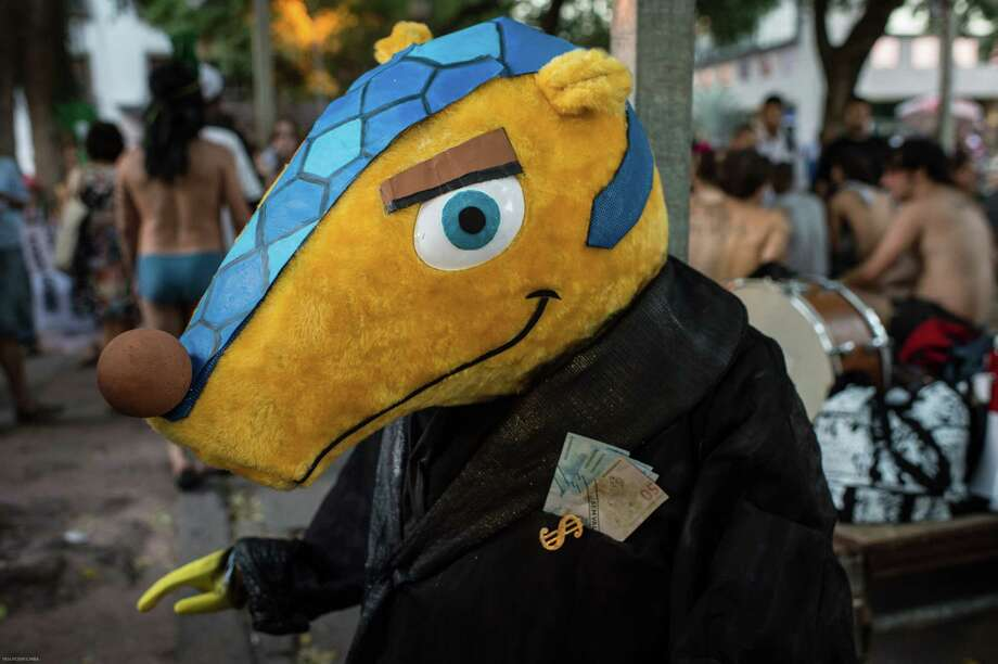 A  mascot of the FIFA World Cup 2014, Tatubola, with imitation cash in pockets is seen during collective movement of occupying carnival  in Rio de Janeiro, Brazil, on Februrary 27, 2014. Rio's carnival will start officially from tomorrow for 5 days and have around 470 groups on streets. Samba school parades will have a peak at Sambodromo on March 2 and 3, 2014.  Photo: YASUYOSHI CHIBA, Getty Images / 2014 AFP
