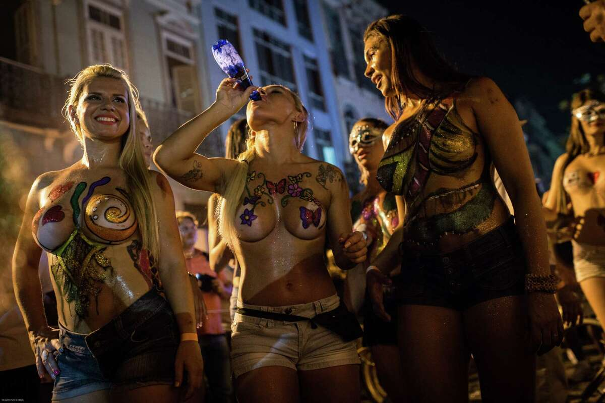 Topless dancers perform during a street parade of Banda da Rua do Mercado in Rio de Janeiro, Brazil, on Februrary 27, 2014. Rio's carnival will start officially from tomorrow for 5 days and have around 470 groups on streets. Samba school parades will have a peak at Sambodromo on March 2 and 3, 2014.