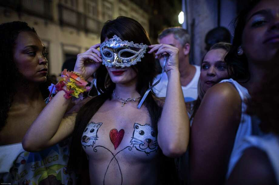 Topless dancers wait for a moment during a street parade of Banda da Rua do Mercado in Rio de Janeiro, Brazil, on Februrary 27, 2014. Rio's carnival will start officially from tomorrow for 5 days and have around 470 groups on streets. Samba school parades will have a peak at Sambodromo on March 2 and 3, 2014.  Photo: AFP, Getty Images / 2014 AFP