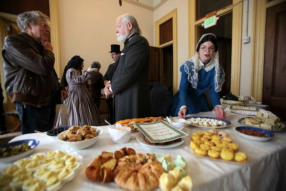 Mike Whitty (left), an adjunct professor at USF, talks with Gov. Leland Stanford (Mike Smith) as Erica Herrington picks up a tray of snacks during the S.F. History Expo at the Old Mint. Photo: Deborah Svoboda, The Chronicle