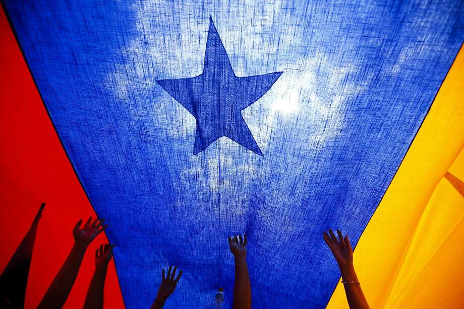Protesters in Caracas hold a Venezuelan flag at a rally against President Nicolas Maduro's government. Photo: Jorge Silva, Reuters