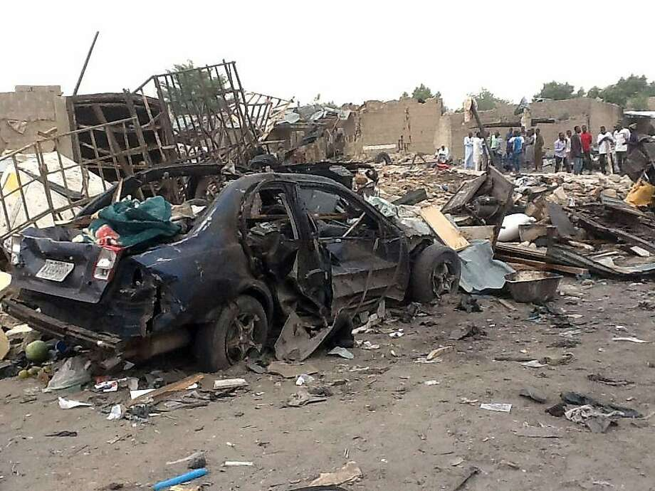 "BEST AVAILABLE QUALITY People gather on March 2, 2014 near the wreckage at the scene where two explosions rocked a crowded neigbourhood in Maiduguri's Gomaris district on the evening of March 1. At least 35 people were killed following two explosions in a crowded neighbourhood of Nigeria's restless northeastern city of Maiduguri, a stronghold of Boko Haram Islamists, police said March 2. ""We are still counting. So far we have counted 35 bodies. Our men are still working with rescue workers at the scene,"" Borno state police commissioner Lawal Tanko said. AFP PHOTO / STRINGERSTRINGER/AFP/Getty Images Photo: Stringer, AFP/Getty Images"