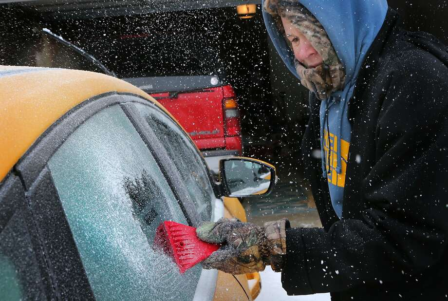 Landon Porter, 15, scrapes ice off his mother's car in St. Charles, Mo., hit hard by a winter storm. Photo: David Carson, Associated Press