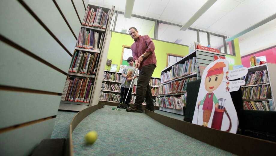 Dylan Gray, 6, and his father, David, golf at Fairfield Woods Library's 2nd annual Mini-Golf Extravaganza on Sunday, March 2, 2014. Photo: BK Angeletti, B.K. Angeletti / Connecticut Post freelance B.K. Angeletti