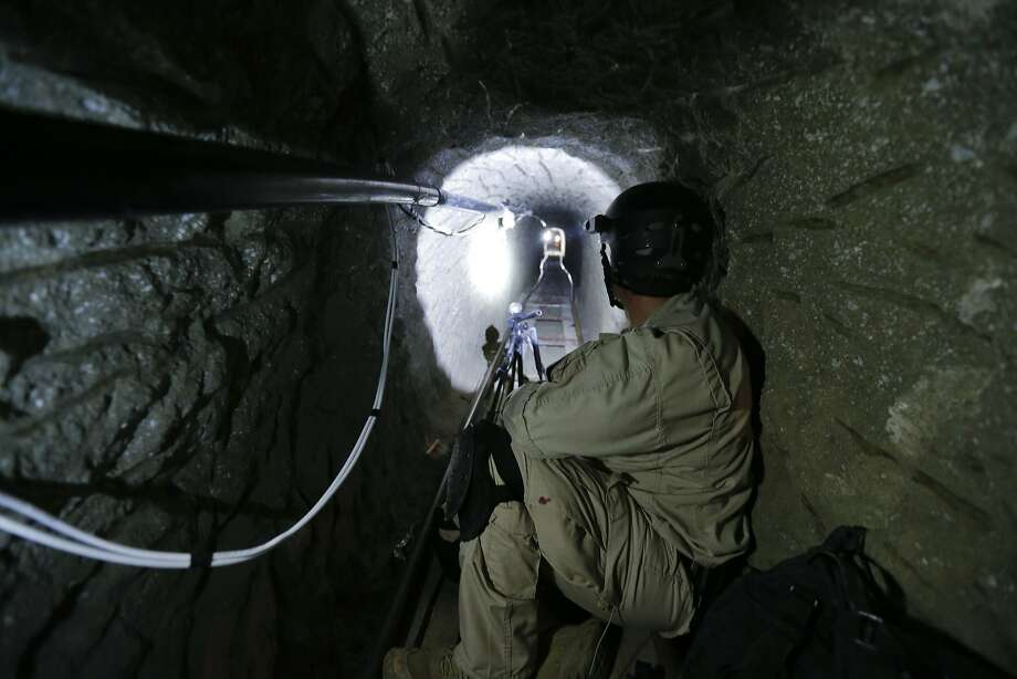 "In photo taken on Nov. 4, 2013, a Homeland Security Investigations member of the special response team looks south in a border tunnel equipped with lighting, ventilation and an electric rail system discovered between Tijuana, Mexico and San Diego in San Diego. Discovered on Oct. 30, 2013, the secret passage on the U.S.-Mexico border was linked by authorities to Mexico's Sinaloa cartel and its leader, Joaquin ""El Chapo"" Guzman, who was arrested on Feb. 22, 2014 in Maztalan, Mexico. (AP Photo/Gregory Bull) Photo: Gregory Bull, Associated Press"