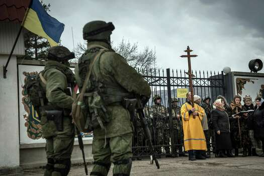 """People sing church songs as unidentified troops block the entrance of a military base in the village of Privolnoye in the Crimea region of Ukraine, March 2, 2014. Russia's move to seize the Crimean Peninsula brought a warning from Ukraine against further incursions. Ukraine's premier said on Sunday that the nation was on the """"brink of disaster."""" Photo: SERGEY PONOMAREV, New York Times / NYTNS"""