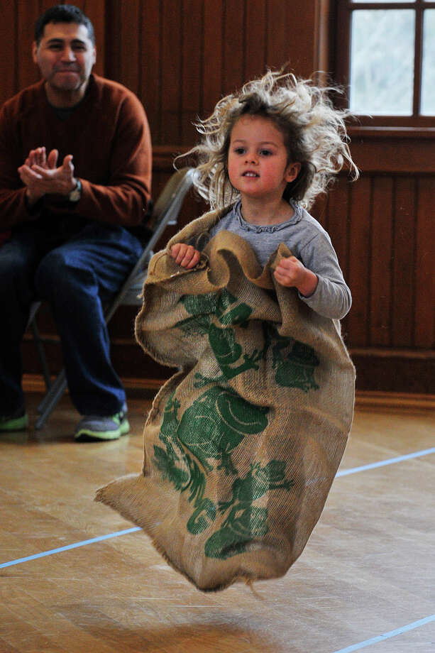 Katy deVeer competes against the clock in the potato sack race during Family Game Day at Round Hill Community House in Greenwich, Conn., on Sunday, March 2, 2014. Photo: Jason Rearick / Stamford Advocate