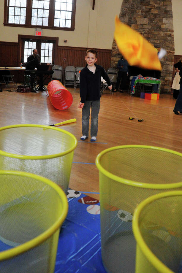 Alexander Piper attempts to land a bean bag in a basket during Family Game Day at Round Hill Community House in Greenwich, Conn., on Sunday, March 2, 2014. Photo: Jason Rearick / Stamford Advocate