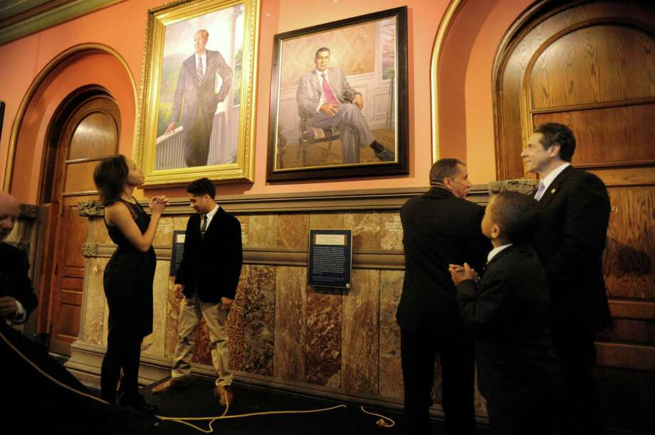 Former Gov. David Paterson, center, is joined, from left, by his stepdaughter Ashley Dennis; his son Alexander Paterson; nephew Carter Paterson; and Gov. Andrew Cuomo for the unveiling of Paterson's official portrait at the Capitol on Sunday, March 2, 2014 in Albany, NY.   The portrait former Gov. George Pataki also can be seen at left.  (Paul Buckowski / Times Union) Photo: Paul Buckowski / 00025960A