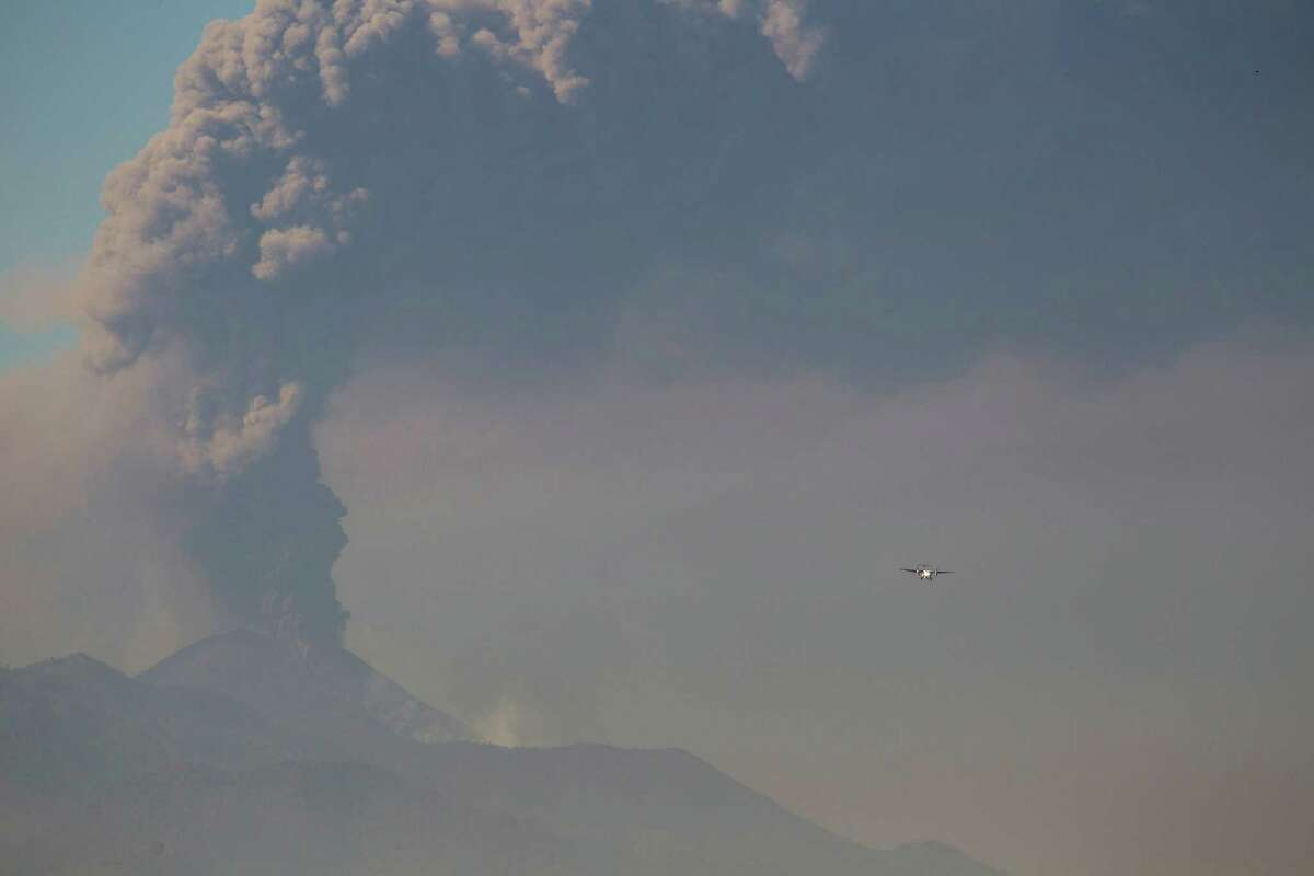 A light aircraft flies towards La Aurora airport in Guatemala City as the Pacaya Volcano spews ash, Sunday, March 2, 2014. column of ash rises from the Pacaya volcano as seen from Villa Nueva, Guatemala, Sunday, March 2, 2014. Guatemala authorities say the Pacaya volcano near Guatemala City has shot plumes of ash and vapor 2.3 miles (3.7 kilometers) high, while spewing glowing-hot rock. The eruption early Sunday is the latest round of activity at the scenic volcano located just 30 miles (50 kms) south of Guatemala City.